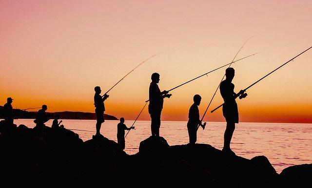 堤防で釣りをす人の影