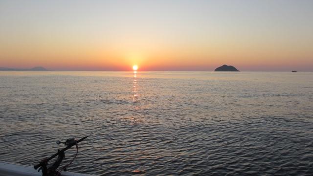 海から登る朝日と釣り竿